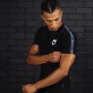 Model draagt zwart DIRE Wovenband T-Shirt met klein DIRE logo
