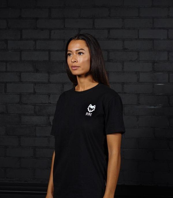 Model draagt DIRE Signature zwart T-shirt met klein wit DIRE logo
